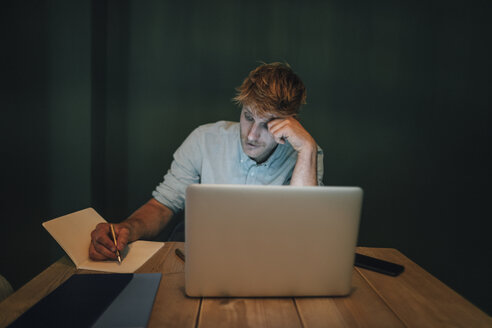 Man sitting in office, working late in his start-up company, taking notes - GUSF01272
