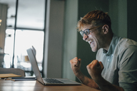 Young man using laptop, laughing happly - GUSF01278