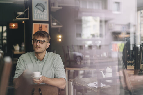 Young business owner sitting in his coffee shop, drinking coffee - GUSF01284