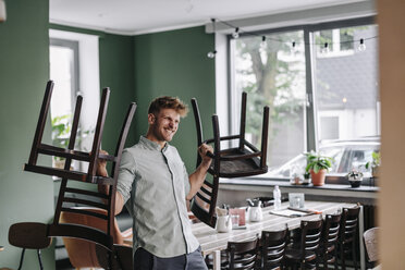 Young business owner lifting chairs - GUSF01287