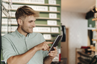 Young business owner using digital tablet in his coffee shop - GUSF01290