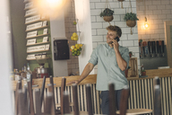 Young man standing at counter in his coffee shop, talking on the phone - GUSF01296