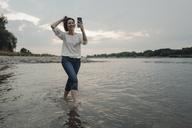 Laughing woman running at the riverside, taking selfies - KNSF04351