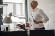 Businessman making noise with drums in his office - KNSF04369