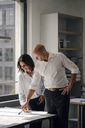 Two architects working in office, discussing blueprints - KNSF04372