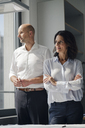 Two architects standing in office, looking out of window - KNSF04375