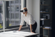 Businessman standing in his office, using VR glasses - KNSF04381