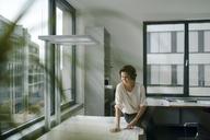 Businesswoman sitting in office, working on blueprints - KNSF04393