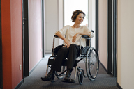 Disabled business woman sitting in wheelchair, with laptop on knees - KNSF04396