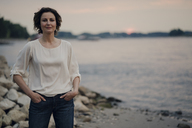 Woman standing at the river at dusk - KNSF04405