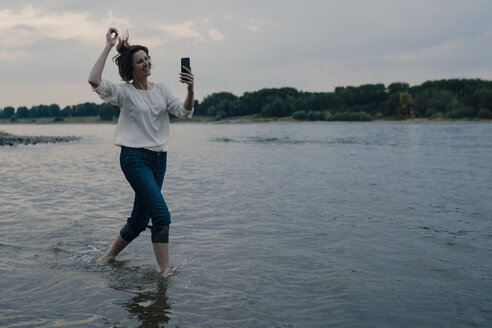 Laughing woman running at the riverside, using smartphone - KNSF04408