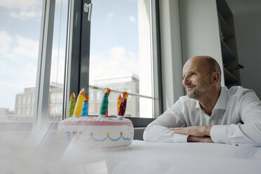 Businessman celebrating his birthday in the office, looking out of window - KNSF04417