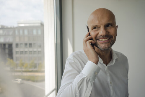 Smiling businessman standing in his office, talking on his mobile phone - KNSF04429