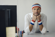 Businessman sitting in office, wearing sweat bands - KNSF04432