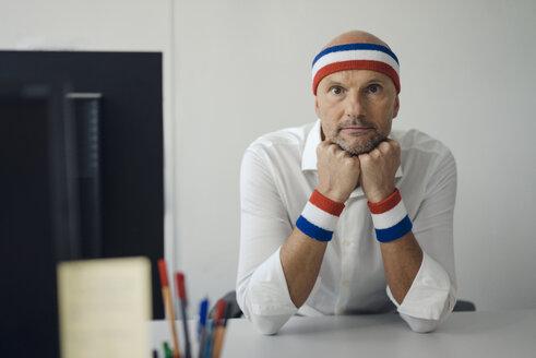 Businessman sitting in office, wearing sweat bands - KNSF04432