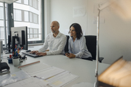 Businessman and woman working together in office - KNSF04438