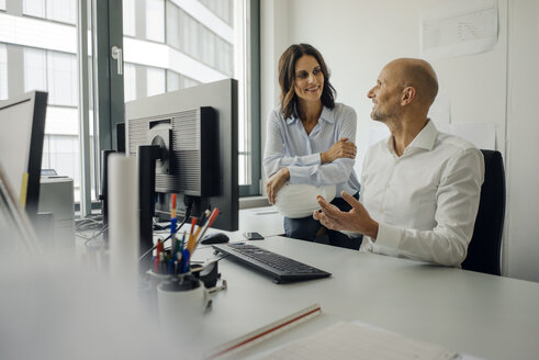 Businessman and woman working together in office - KNSF04441