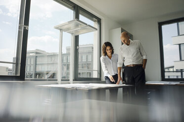 Two architects working in office, discussing blueprints - KNSF04453