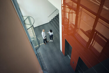 Business people talking in front of elevator - KNSF04474