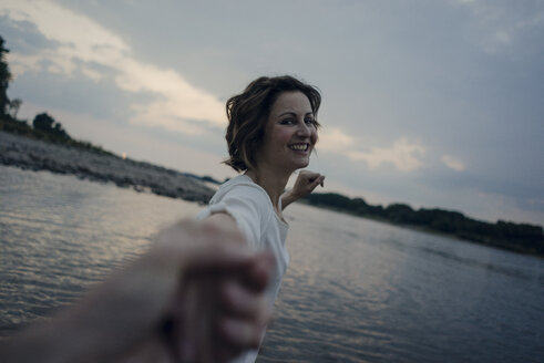 Laughing woman holding hands at the river - KNSF04483