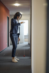 Mature businesswoman standing in office corridor, playing with yoyo - KNSF04501