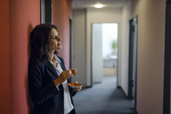 Mature businesswoman standing in office corridor, drinking coffee - KNSF04504