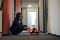 Mature businesswoman sitting in office corridor, putting on roller skates - KNSF04507