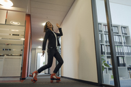 Mature businesswoman rollerskating in office corridor - KNSF04510