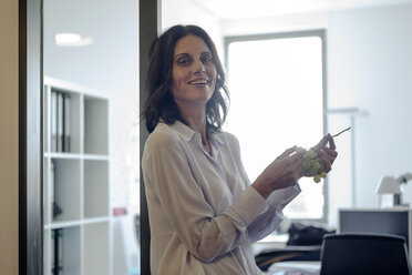 Businesswoman standing in office, eating grapes - KNSF04513