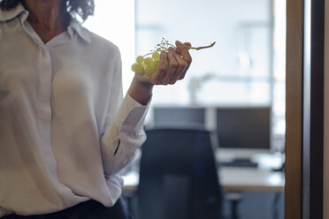Businesswoman standing in office, eating grapes - KNSF04516