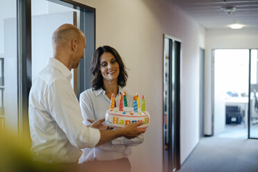 Businessman gifting his colleague with a birthday cake in office - KNSF04522