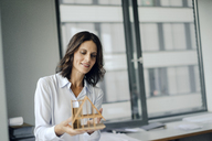 Businesswoman holding architectural model of a house - KNSF04528
