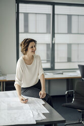 Businesswoman sitting in office, working on blueprints - KNSF04540