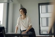 Successful businesswoman sitting on desk in her office - KNSF04543