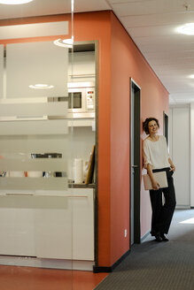 Laughing businesswoman standing in office corridor, holding laptop - KNSF04546