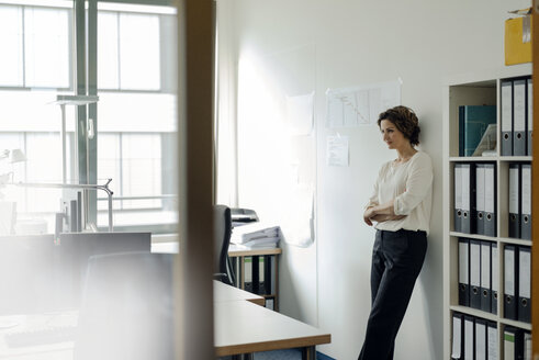 Businesswoman leaning against wall in office, with arms crossed - KNSF04555