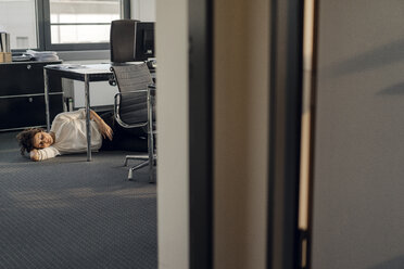 Tired businesswoman sleeping on floor under her desk - KNSF04564