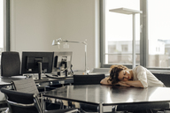 Tired businesswoman sleeping on her desk - KNSF04567
