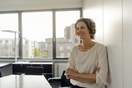Businesswoman leaning against wall in office, with arms crossed, smiling - KNSF04570