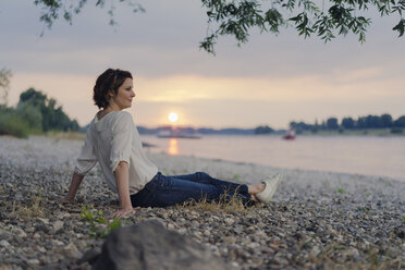 Woman sitting at the river, watching sunset - KNSF04582