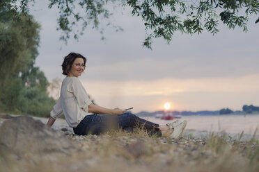 Woman sitting at the river, watching sunset - KNSF04585