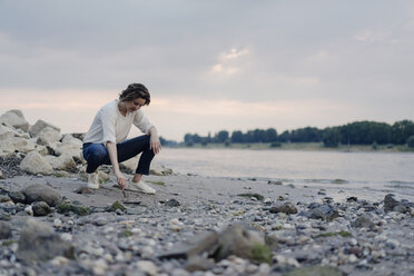 Woman crouching at the riverside, drawing in sand with a stick - KNSF04588