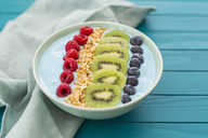Smoothie bowl with blueberries, raspberries, kiwi and chopped hazelnuts - JUNF01099