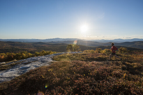 Trail running along the summit of Foss Mt. with the setting sun and White Mountains in the background. - AURF02251