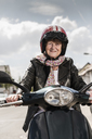 Active senior lady riding motor scooter in the city - UUF14913