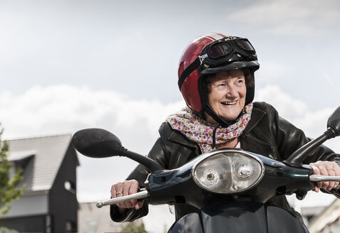 Active senior lady riding motor scooter in the city - UUF14916