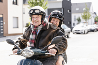 Happy senior couple riding motor scooter - UUF14919