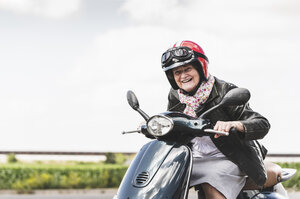 Active senior lady riding motor scooter on the road - UUF14931