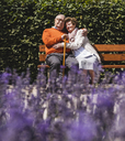 Senior couple sitting on bench in a park, with arms around - UUF14934