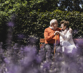 Senior couple sitting on bench in a park, falling in love - UUF14937